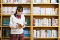 本棚にもたれて本を読む女子学生