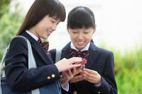 スマートフォンを見る中高生