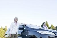 車の横で眺めを楽しむシニア夫婦