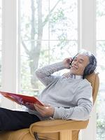 ヘッドホンで音楽を聴く中高年日本人男性