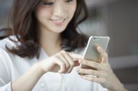 カフェでスマートフォンを操作する日本人女性