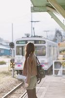 駅で電車を待つ一人旅の日本人女性