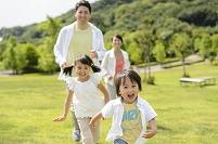 新緑の公園で駆けっこする日本人家族