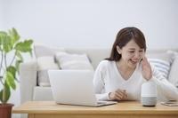 AIスピーカーに話かける日本人女性
