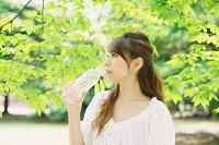 新緑と水を飲む日本人女性