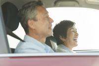 ドライブ旅行をするシニアカップル