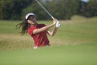 アプローチショットを打つ女子ゴルフ選手