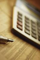 新聞の株式欄と万年筆と電卓