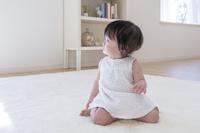 カーペットに座って見つめる日本人の赤ちゃん