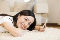寝転がってスマホを見る日本人女性