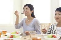 おいしそうにカレーを食べるお母さんと子供