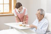シニアの食事を手伝う介護士