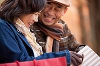 ベンチに座って買い物袋の中を見る中高年夫婦