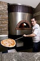 ピザ窯からピザを出す料理人