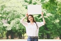 公園にホワイトボードを持つ日本人女性
