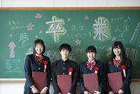 卒業証書を持ち微笑む学生
