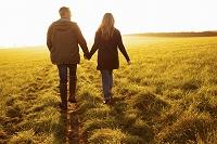 草原を手をつないで歩くカップル