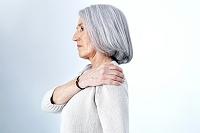 肩を触るシニア女性