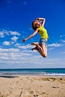 青空と海とジャンプする日本人女性