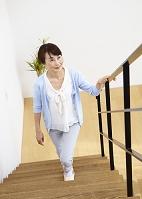 階段をのぼるシニアの日本人女性