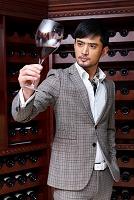 ワイングラスを見る男性