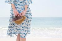 女性のサンダルと海