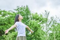 新緑と手を広げる日本人女性