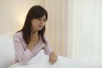 体調不良で喉を押さえる日本人女性