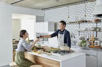キッチンでワインを乾杯する日本人夫婦