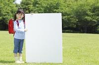 新緑の中ホワイトボードを持つランドセルの日本人の女の子