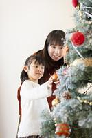 クリスマスツリーの飾り付けをする親子