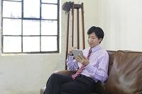 ソファーで寛ぎながら仕事をする日本人ビジネスマン