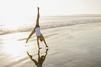 ビーチで側転をする外国人女性