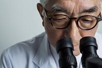 顕微鏡を覗く70代研究員
