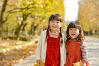 公園の並木道で落ち葉を持った女の子