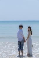 波打ち際で手を繋ぐカップル