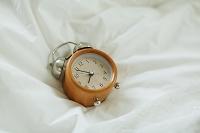 白いベッドの上の目覚まし時計