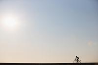 太陽とサイクリングする女性
