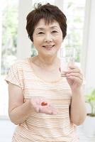 薬とコップを持つ中高年女性