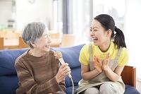 カラオケを楽しむおばあちゃんと介護士の日本人女性