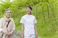 公園を散歩するシニア女性と女性介護士