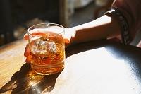 ウイスキーグラスを持つ女性の手
