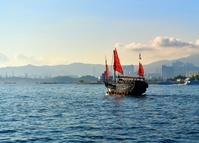 中国 香港ビクトリア・ハーバーのビル群と赤い帆船