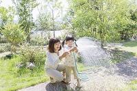 ホースで水まきする日本人親子
