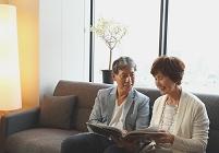 ソファーで読書する日本人のシニア夫婦