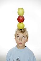 彼の頭の上にリンゴをのせた男の子