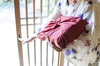 風呂敷包みを持つ浴衣の女性