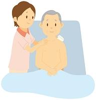 ベッドで体を拭いてもらう老人男性と介護士