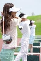 ゴルフ練習場でスイングする男女