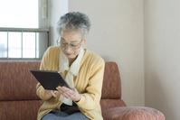 タブレットを操作するシニアの日本人女性
